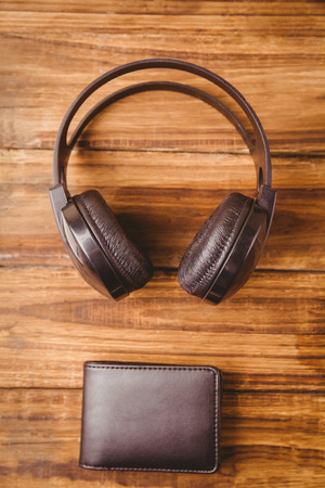 coordinating: Music headphone next to wallet wooden table