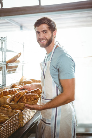 happy worker: happy worker holding a basket of croissant  at the bakerie
