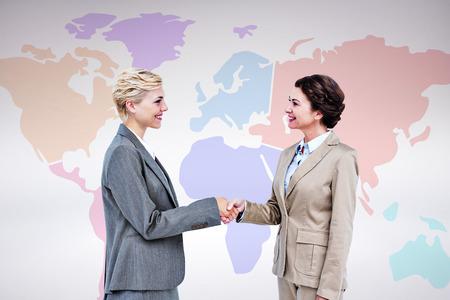 business handshake: Smiling women shaking hands against grey background Stock Photo