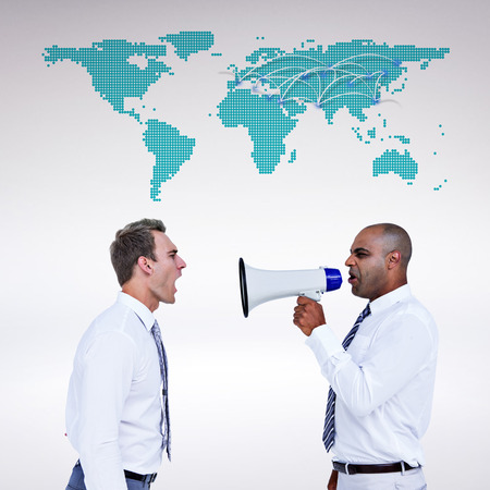 businessman using a megaphone: Businessman yelling with a megaphone at his colleague against world map
