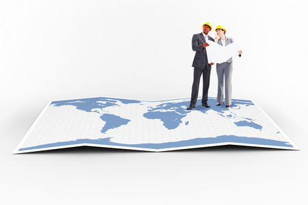 hard hats: Business people wearing hard hats are discussing  against world map