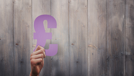 pound sign: Hand holding pound sign against pale grey wooden planks Stock Photo