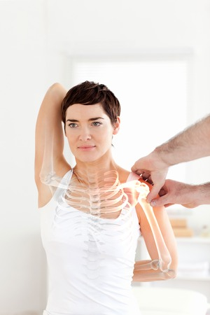 Digital composite of Highlighted bones of woman at physiotherapist Archivio Fotografico