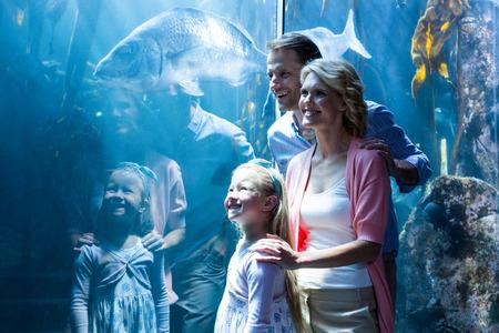 pez pecera: Familia feliz mirando en un tanque en el acuario