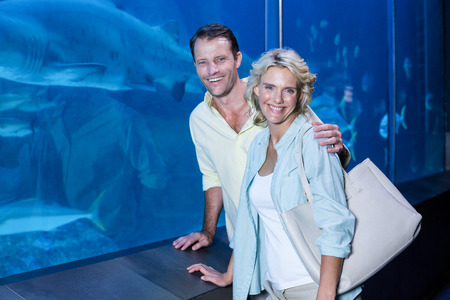 fishtank: Happy couple looking at camera beside the fish tank at the aquarium Stock Photo