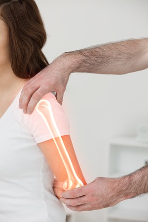 digital composite: Digital composite of Highlighted bones of woman at physiotherapist Stock Photo