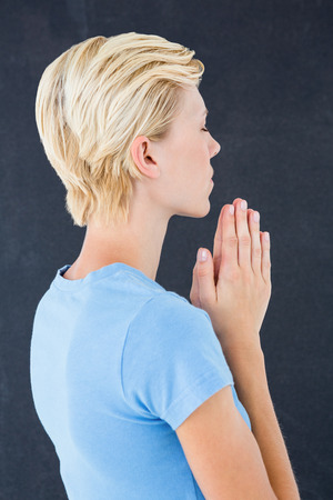 jehovah: Pretty blond woman praying on black background