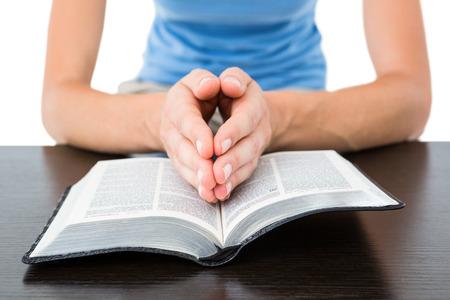 biblia: Mujer rezando durante la lectura de la biblia en el fondo blanco Foto de archivo