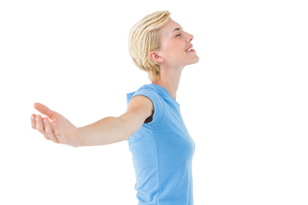 escapism: Blonde woman standing arms outstretched on white background Stock Photo