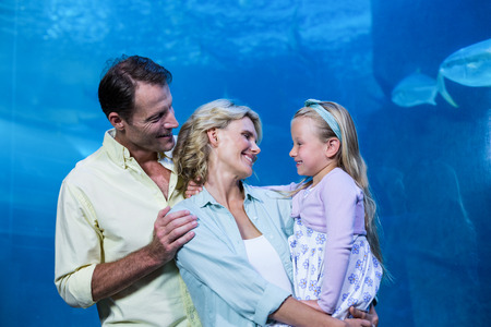 fishtank: Happy family smiling at each other beside the fish tank