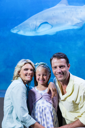 fishtank: Happy family looking at camera beside the fish tank at the aquarium