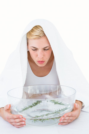 Blonde woman inhaling herbal medicine on white background Stock Photo