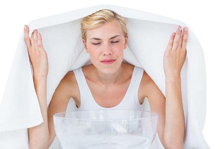 Blonde woman inhaling herbal medicine on white background Stockfoto