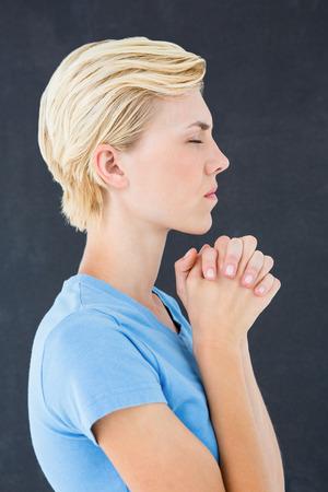 mujeres orando: Mujer rubia bastante rezando sobre fondo negro