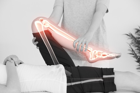 bone health: Digital composite of Highlighted bones of woman at physiotherapist Stock Photo