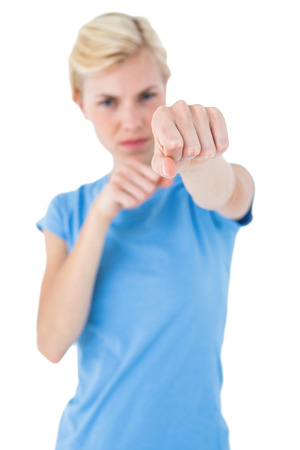 punched out: Stern blonde woman pointing with her finger on white background Stock Photo