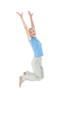 escapism: Cheerful blonde woman jumping on white background