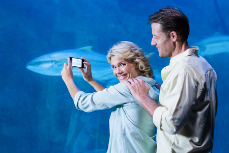 fishtank: Happy couple taking a picture of fishes at the aquarium Stock Photo