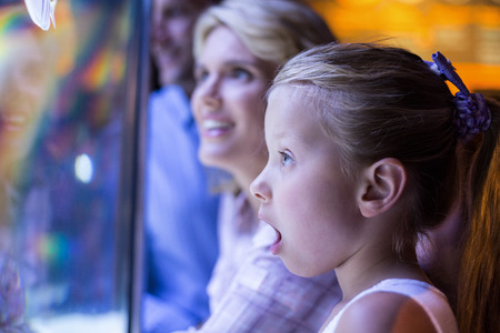 aquarium: Surprised daughter behind a starfish tank at the aquarium