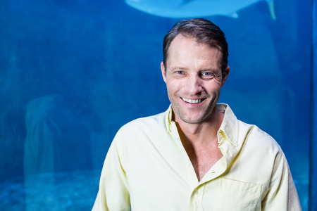 fishtank: Happy man looking at camera beside the fish tank at the aquarium