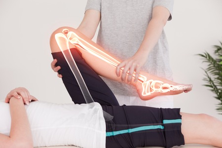 physiotherapist: Digital composite of Highlighted bones of woman at physiotherapist Stock Photo