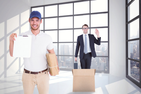 delivery room: Happy delivery man holding cardboard box and clipboard against room with large window showing city Stock Photo