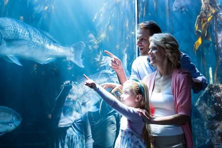 Happy family pointing a fish in the tank at the aquarium