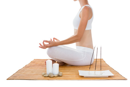 alternative therapy: Fit woman meditating on bamboo mat on white background