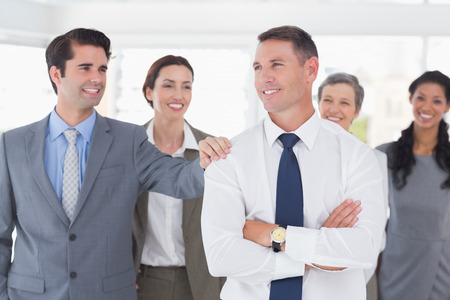 congratulating: Business people congratulating their colleague in the office