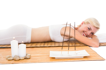 bamboo mat: Attractive blonde woman resting on bamboo mat on white background