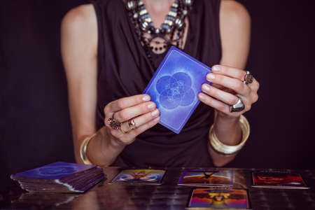 telepathy: Fortune teller forecasting the future with tarot cards on black background