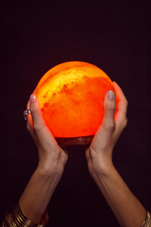 telepathy: Fortune teller holding crystal ball on black background Stock Photo