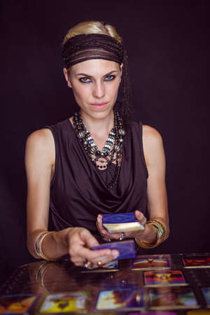 forecasting: Fortune teller forecasting the future with tarot cards on black background