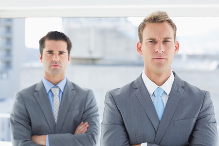 frowning: Two businessmen frowning at camera in the office