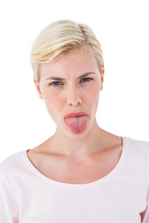 sticking out tongue: Blonde woman sticking her tongue out on white background