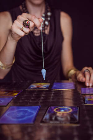 forecasting: Fortune teller forecasting the future with pendulum on black background
