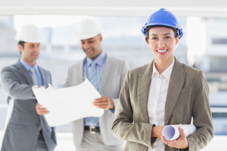hard hats: Businessmen and a woman with hard hats holding blueprint in the office Stock Photo