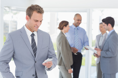 happy business team: Businessman texting while his colleagues discussing in the office