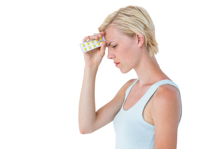 Attractive woman having headache and holding pack of pills on white background