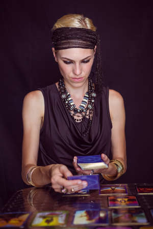telepathy cards: Fortune teller forecasting the future with tarot cards on black background