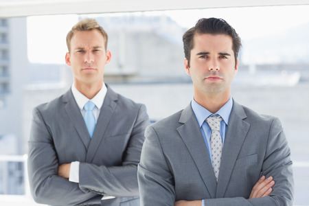 stylish man: Two businessmen frowning at camera in the office