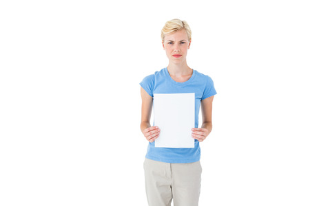 stern: Stern blonde woman holding sheet of paper on white background Stock Photo