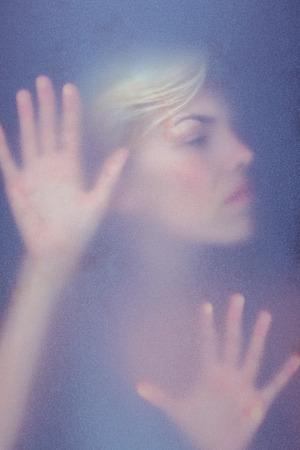 desolaci�n: Mujer rubia tocar vidrio esmerilado en la sombra Foto de archivo