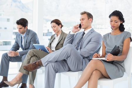 mobile technology: Business people sitting and waiting in the office