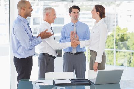 congratulating: Business team congratulating their colleague in the office Stock Photo