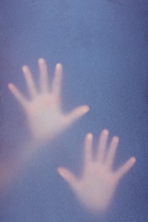 dreariness: Hands touching frosted glass in the shadow