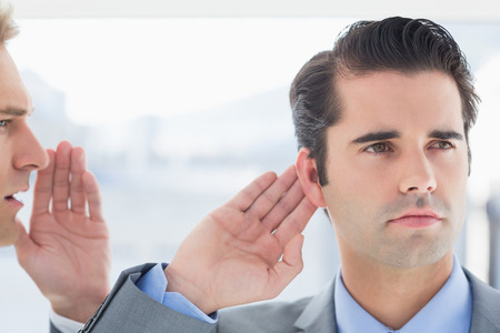 Businessman telling secret to his colleague in the office