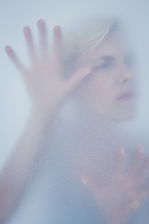 wistfulness: Blonde woman touching frosted glass in the shadow