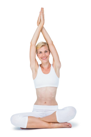 mujer meditando: Fit mujer sonriente meditando sobre fondo blanco