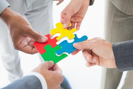 piezas de puzzle: Compa�eros de trabajo que llevan a cabo pieza del rompecabezas en la oficina